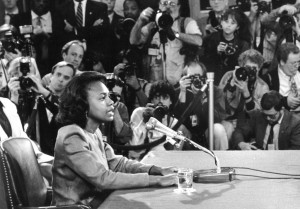 Anita Hill testifying before the Senate Judiciary Committee on Capitol Hill. A portion of the photo gallery is in the background.